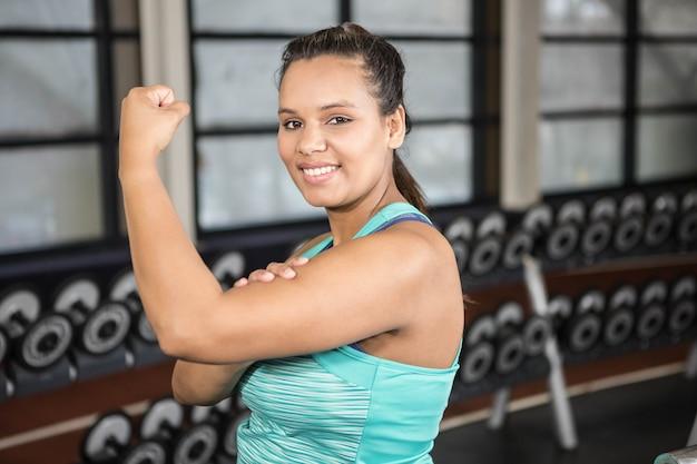 Mulher sorridente, em, sportswear, mostrando, dela, músculos, em, a, ginásio