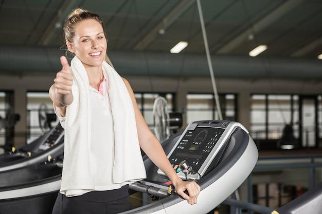 Mulher sorridente, em, sportswear, mostrando, polegar, cima, em, a, ginásio