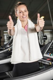 Mulher sorridente, em, sportswear, mostrando, polegares cima, em, a, ginásio
