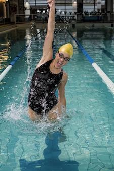 Mulher sorridente, em, swimsuit, pular, em, a, piscina