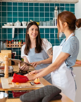 Mulher sorridente em tiro médio na cozinha Foto Premium