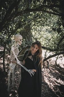 Mulher sorridente, em, traje bruxa, segurando, acima, esqueleto cabeça
