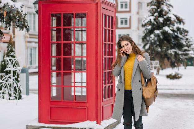 Mulher sorridente em traje elegante, falando no smartphone em pé perto da cabine telefônica britânica no inverno. foto ao ar livre de mulher morena satisfeita no casaco da moda, carregando a mochila marrom durante a caminhada.