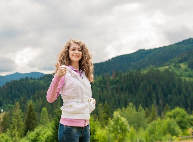 Mulher sorridente em um campo com o polegar para cima