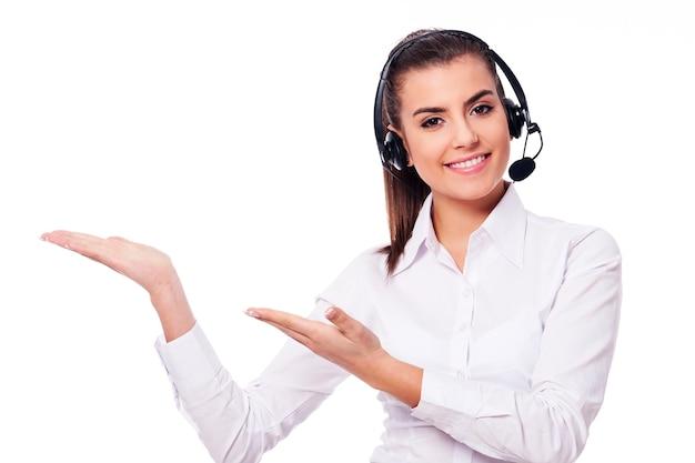 Mulher sorridente em um fone de ouvido apresentando algo