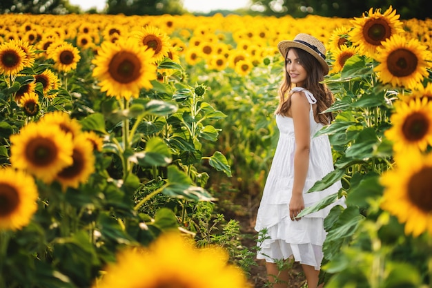 Mulher sorridente em um vestido branco andando em um campo de girassóis. ideal para publicidade e foto sol brilha brilhante e suculento