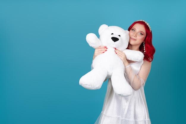 Mulher sorridente em um vestido branco pressiona um grande ursinho de pelúcia branco contra o rosto