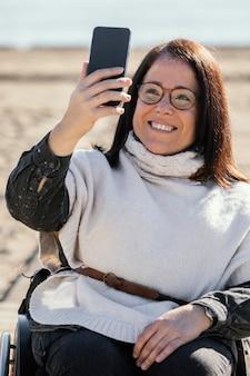 Mulher sorridente em uma cadeira de rodas tirando uma selfie na praia