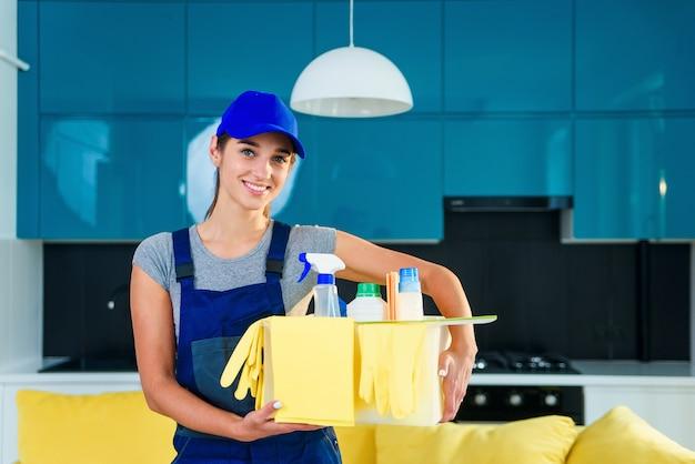 Mulher sorridente em uniforme especial para limpeza de apartamento mantém a caixa com detergentes, luvas, panos e em pé na cozinha moderna e elegante.