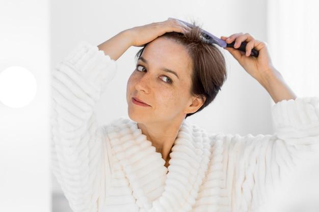 Mulher sorridente em vista frontal escovando o cabelo