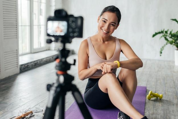 Mulher sorridente em vlogging de roupas esportivas