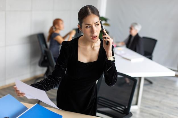 Mulher sorridente empresário asiático ocupado trabalhando, falando no celular no escritório em casa. espaço de cópia do fundo do banner