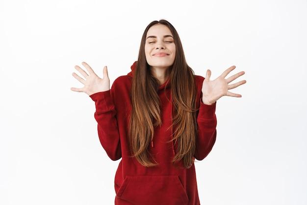 Mulher sorridente encantada fecha os olhos e sente satisfação, levantando as mãos e respirando o ar livremente, em pé feliz e despreocupada, regozijando-se, em pé sobre uma parede branca