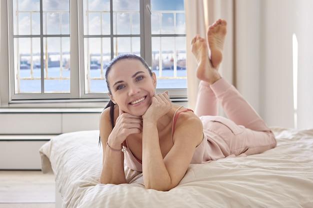 Mulher sorridente encontra-se de bruços na cama.