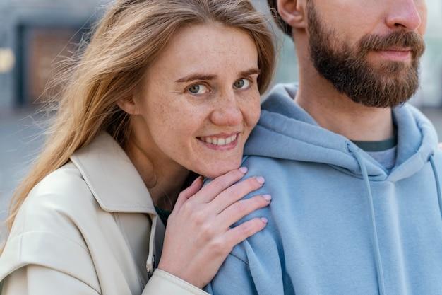 Mulher sorridente encostada em um homem ao ar livre
