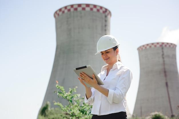 Mulher sorridente engenheiro com tablet na estação elétrica.