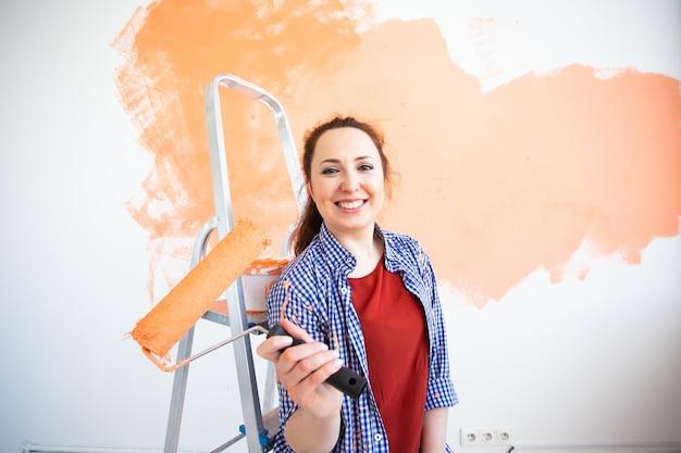 Mulher sorridente engraçada pintando a parede interior de casa com rolo de pintura