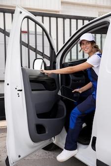 Mulher sorridente entregadora na van