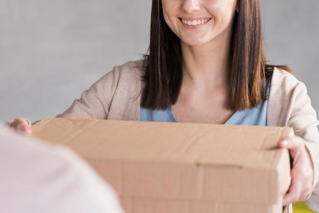 Mulher sorridente, entregando a caixa de papelão