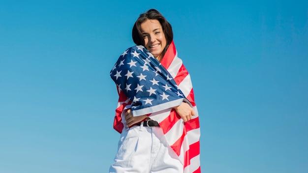 Mulher sorridente, envolvendo grande bandeira dos eua em torno de si