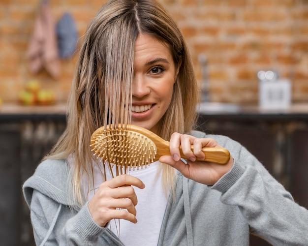 Mulher sorridente escovando o cabelo emaranhado