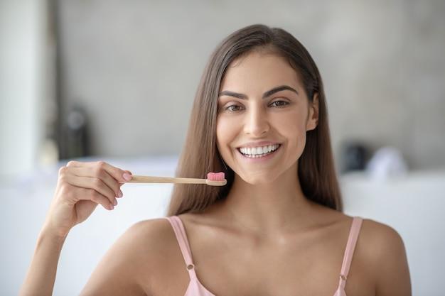 Mulher sorridente escovando os dentes com uma escova de bambu