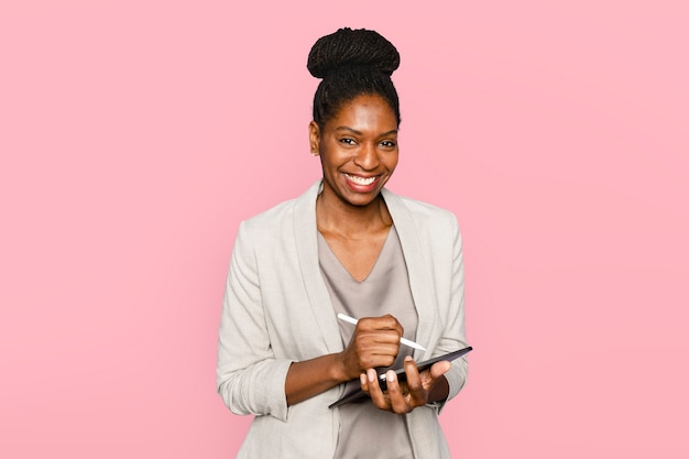 Mulher sorridente escrevendo notas em um tablet digital