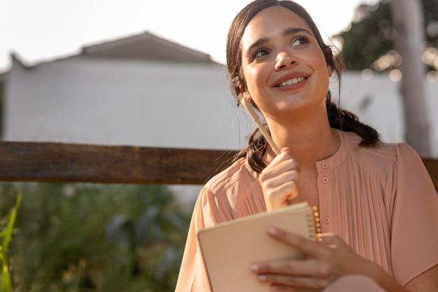 Mulher sorridente escrevendo plano médio