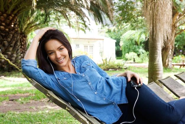 Mulher sorridente, escutar música, com, fones ouvido