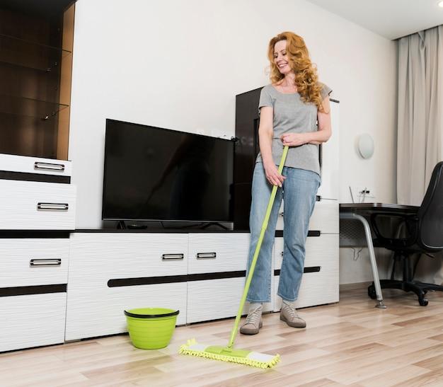 Mulher sorridente, esfregando o chão