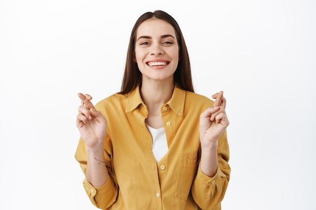 Mulher sorridente esperançosa cruza os dedos e espera pelos resultados, esperança de boa sorte, de pé otimista contra uma parede branca