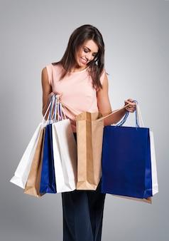 Mulher sorridente espiando dentro das sacolas de compras