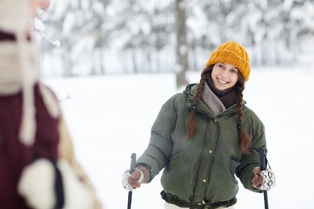 Mulher sorridente, esquiar na floresta