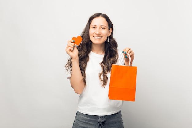 Mulher sorridente está segurando a sacola de compras laranja e o coração sobre fundo branco.