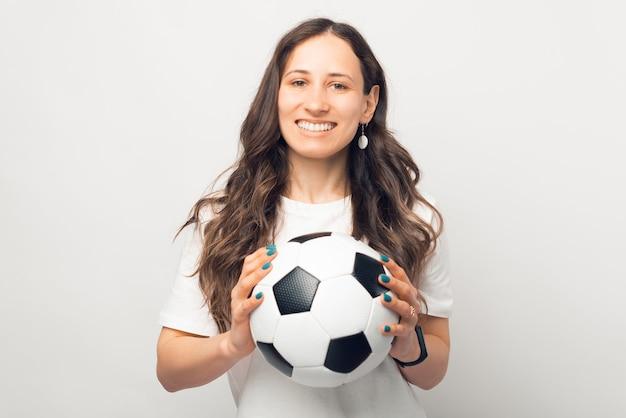 Mulher sorridente está segurando uma bola de futebol e olhando para a câmera.
