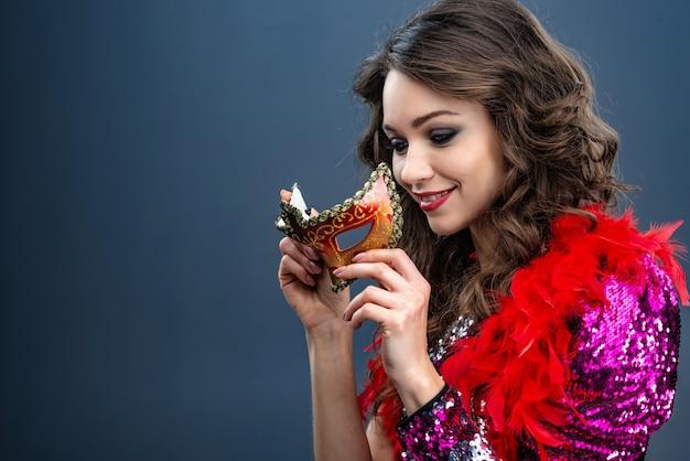 Mulher sorridente está segurando uma máscara de carnaval em um vestido brilhante