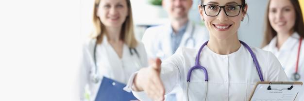 Mulher sorridente estende a mão para um aperto de mão atrás de sua equipe de médicos