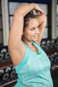 Mulher sorridente, esticando os braços no sportswear no ginásio