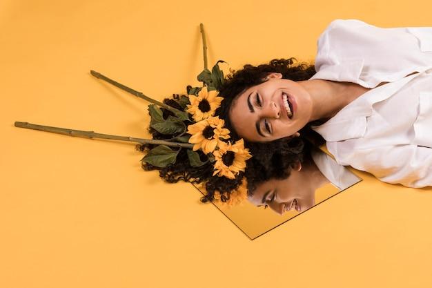 Mulher sorridente étnica atraente com flores no espelho
