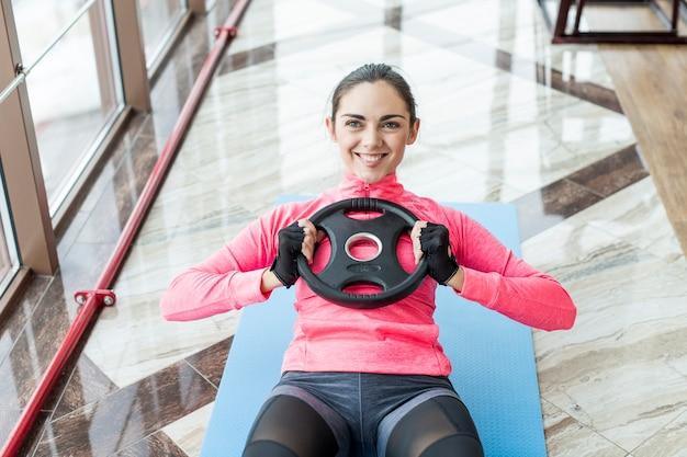 Mulher sorridente, exercitar, abs, com, peso, prato