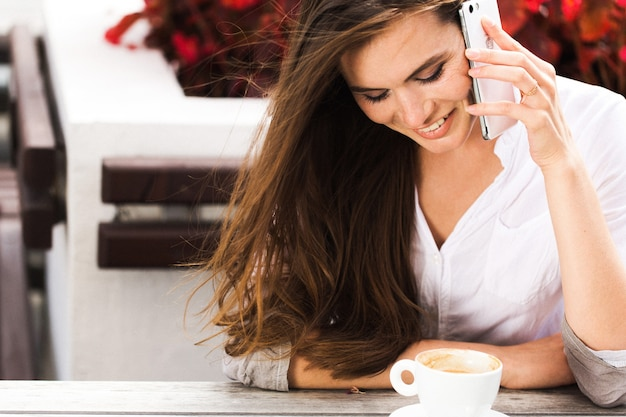 Mulher sorridente fala no telefone