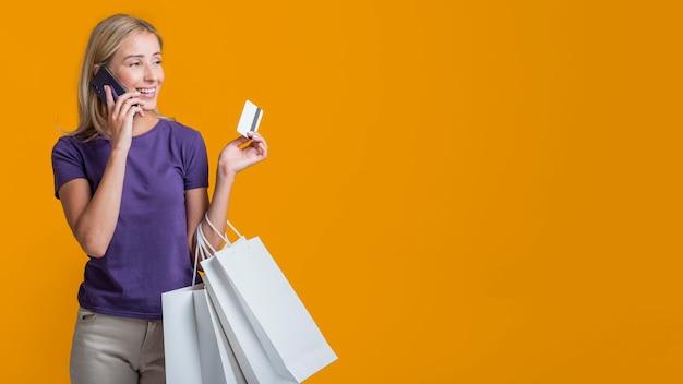 Mulher sorridente falando ao telefone e segurando um cartão de crédito e sacolas de compras