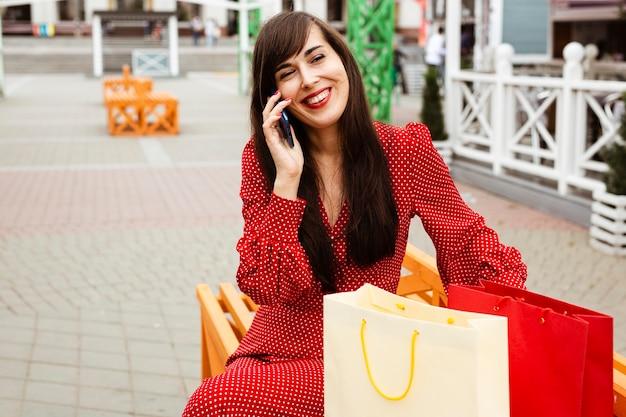 Mulher sorridente falando ao telefone enquanto está sentada ao lado de sacolas de compras