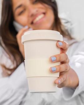 Mulher sorridente falando ao telefone enquanto segura a xícara de café