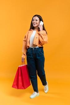 Mulher sorridente falando ao telefone enquanto segura sacolas de compras