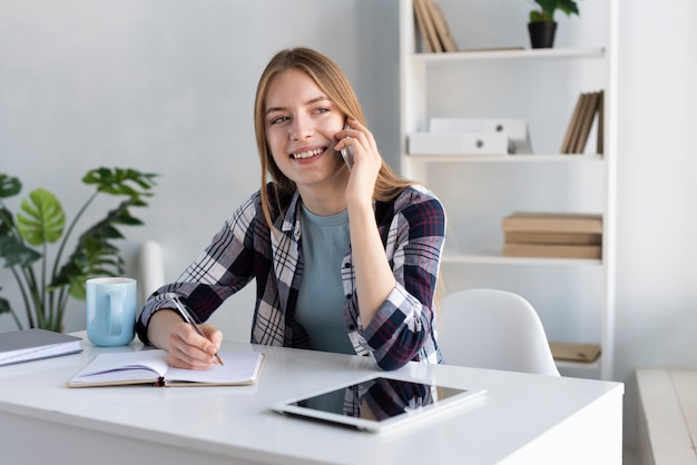 Mulher sorridente, falando ao telefone na mesa dela