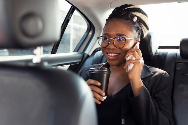 Mulher sorridente falando ao telefone no banco de trás do carro enquanto toma café