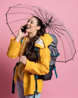Mulher sorridente, falando ao telefone, segurando um guarda-chuva