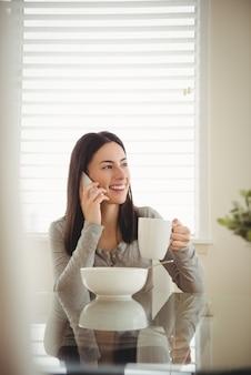 Mulher sorridente falando no celular enquanto toma o café da manhã