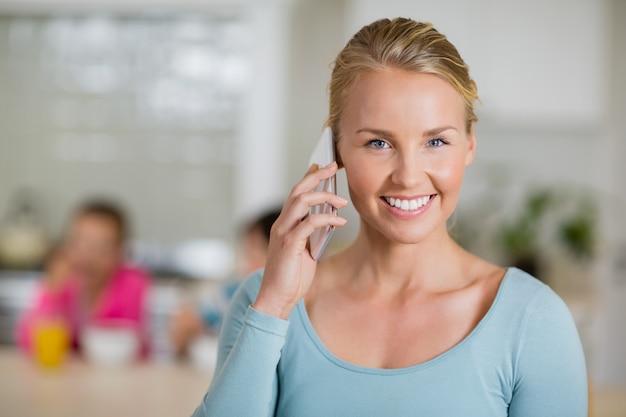 Mulher sorridente, falando no celular na cozinha